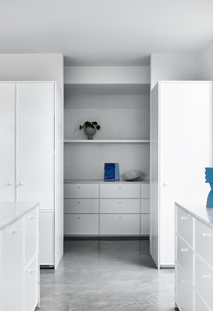 Concealing the kitchen appliances behind custom joinery allows the kitchen to fade into the background when not in use. Bianco Gioia marble countertops and Glazed Square Mosaic tiles from Academy Tiles enhance the clean white look.