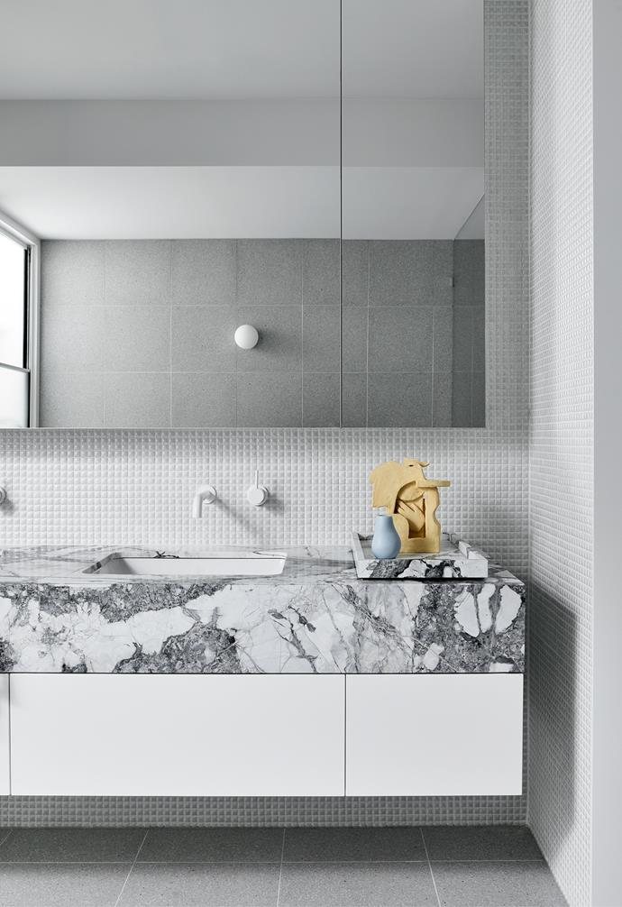 Richly veined Concordia marble, block-white cabinetry and teeny INAX mosaic tiles give the guest bathroom its own personality without deviating from the home's overall scheme.