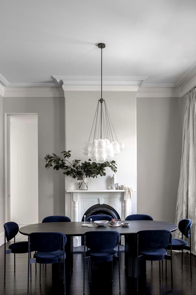"""A Gubi 'Half Moon' table from Cult Design is surrounded by Verpan 'series 430' chairs from Great Dane. The existing fireplace was restored. Apparatus'Cloud 19' chandelier, Criteria. """"This is a house that's so calm and inviting,"""" says Belinda. """"It's a real haven."""""""