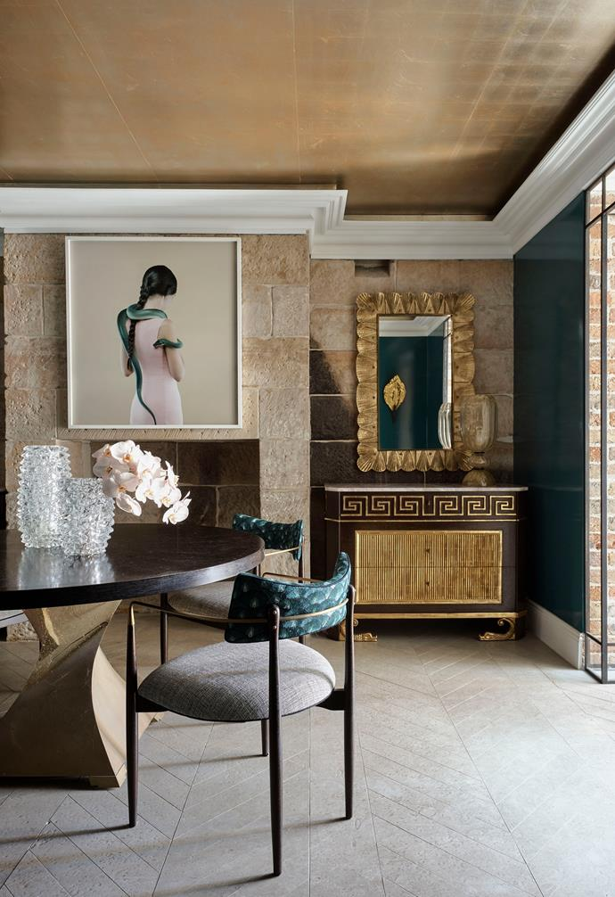 """Cleopatra, 2019 by Petrina Hicks from Michael Reid Sydney makes a statement on the original [sandstone wall](https://www.homestolove.com.au/stone-feature-walls-21461 target=""""_blank""""), which has been refurbished. Mirror from Conley & Co hangs above a custom 'Dolphin' commode in lacewood veneer from Dessin Fournir, Los Angeles. 'Twister' table base in brass from Scala Luxury, LA, with a custom rift oak top by Thomas Hamel & Associates. Kelly Wearstler 'Elliott' dining chairs with a burnished brass finish and upholstered in Décor de Paris 'Bargello' in Black Aqua. Handpainted 'Metal Leaf' ceiling finish in White Fire by David Bonk, San Francisco. Flooring is Thala sandstone in a herringbone pattern from Worldstone. Clients' own vases."""