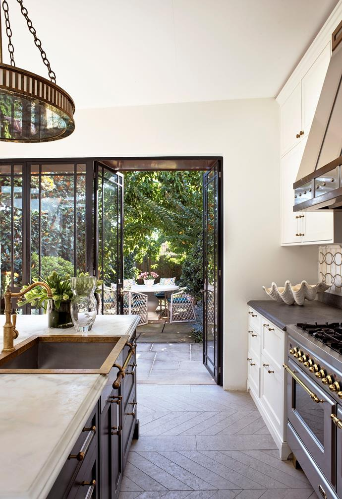 The kitchen was relocated several times but now occupies the perfect position in the new extension leading to the garden. Custom cabinetry by Thomas Hamel & Associates in Dulux 'Domino' by Joinery Group with Pietra Cardosa stone benchtop and Calacatta Oro marble island benchtop from Worldstone.