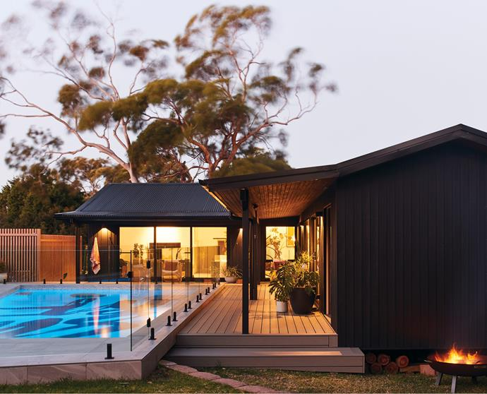 The blue pool, together with warm greys from the Trex decking and pool coping, softens their all-black home.