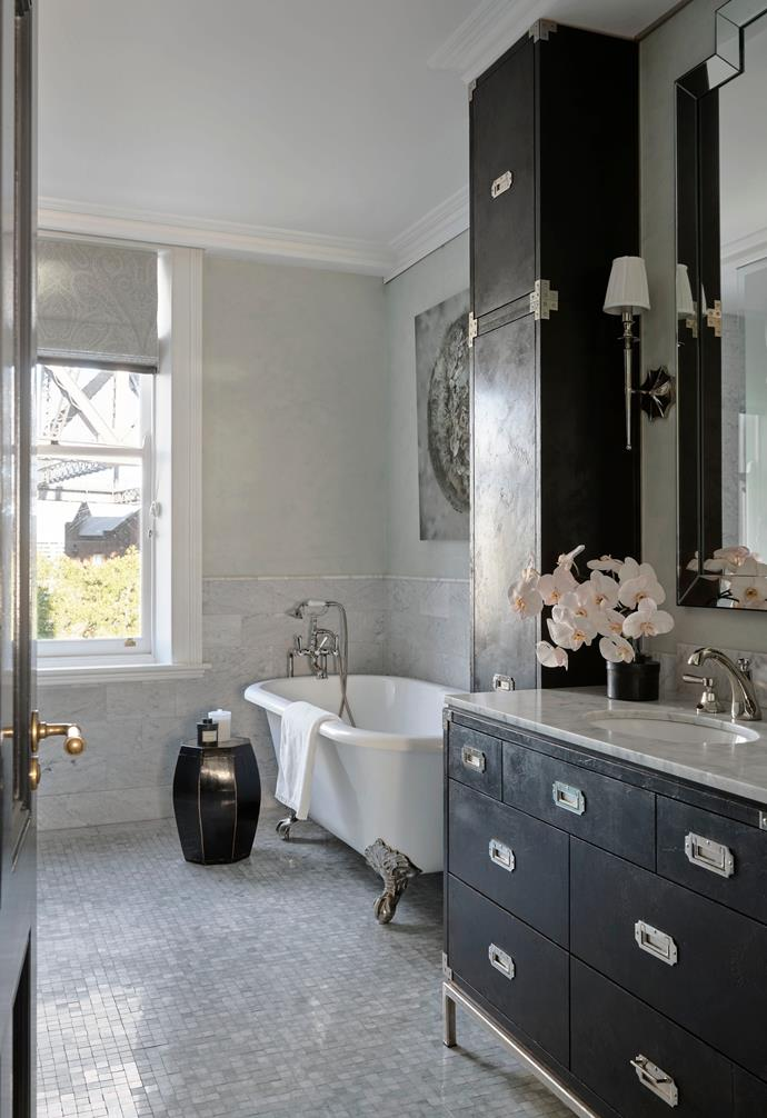 The guest bathroom has a custom mirror and vanity by Thomas Hamel & Associates in black lacquer with a Carrara stone top from Worldstone. Hudson Valley 'Ellery' wall light from LightCo. Devon&Devon 'Admiral Lux' bath and Brodware 'Classique' tapware from Candana. 'Ming' mosaic floor tiles from The Fine Line, Chicago, and Carrara marble brick bond wall tiles from Worldstone below a stucco polished-plaster finished in pale mint. Artwork, Guthega by Catherine Nelson from Michael Reid Sydney.