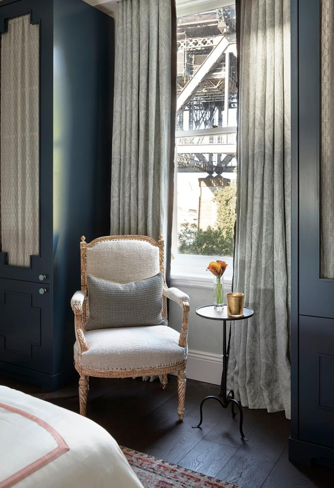 The guest suite on the top floor enjoys a bird's eye view of the Sydney Harbour Bridge. Louis XIV armchair from The Vault Sydney. Cushion in Dedar 'Twist Again' in Pétrole with trim in 'Oberon' twisted cord by Samuel & Sons from South Pacific Fabrics. Clients' side table. Custom curtains by Thomas Hamel & Associates in de Le Cuona 'Florence' in Haze from Boyac with an 'RTC Boulette' fringe in Twilight by Samuel & Sons from South Pacific Fabrics. Custom joinery by Bober.