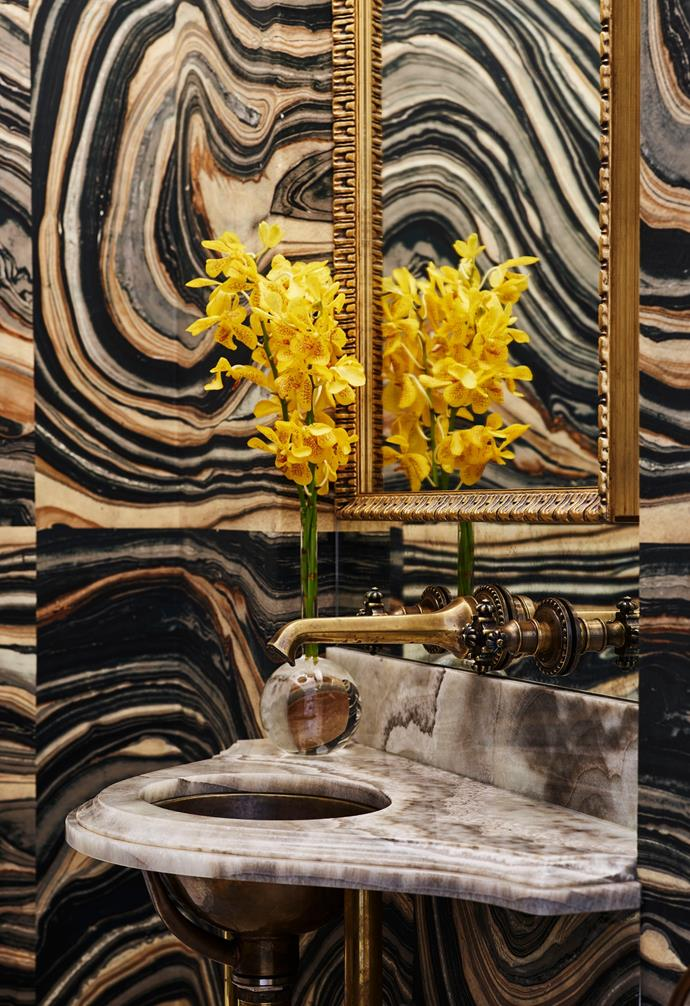 The powder room has 'Swirls' wallpaper in Green Black from Robert Crowder & Co, California. Silver onyx basin surround from Worldstone with 'Normandy Drop' hammered copper sink from Waterworks, LA, and Cruciform antique brass tapware from Compass Stone, London. Custom mirror from Acme Framing.