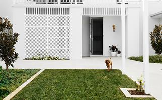 White Hamptons style home exterior with manicured lawn