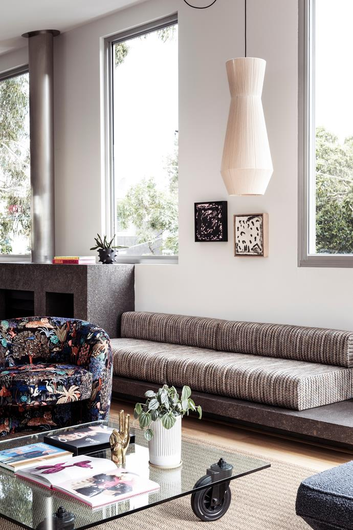 In her upstairs living space, a custom fireplace seat by Harbro Furniture has been upholstered in Misia fabric from The Textile Company, a Ren Weaver pendant from Pop & Scott hangs above and a glass coffee table on wheels lends an industrial New York edge. The two artworks are by Sean Bailey (left) and Irene Grishin Selzer (right).
