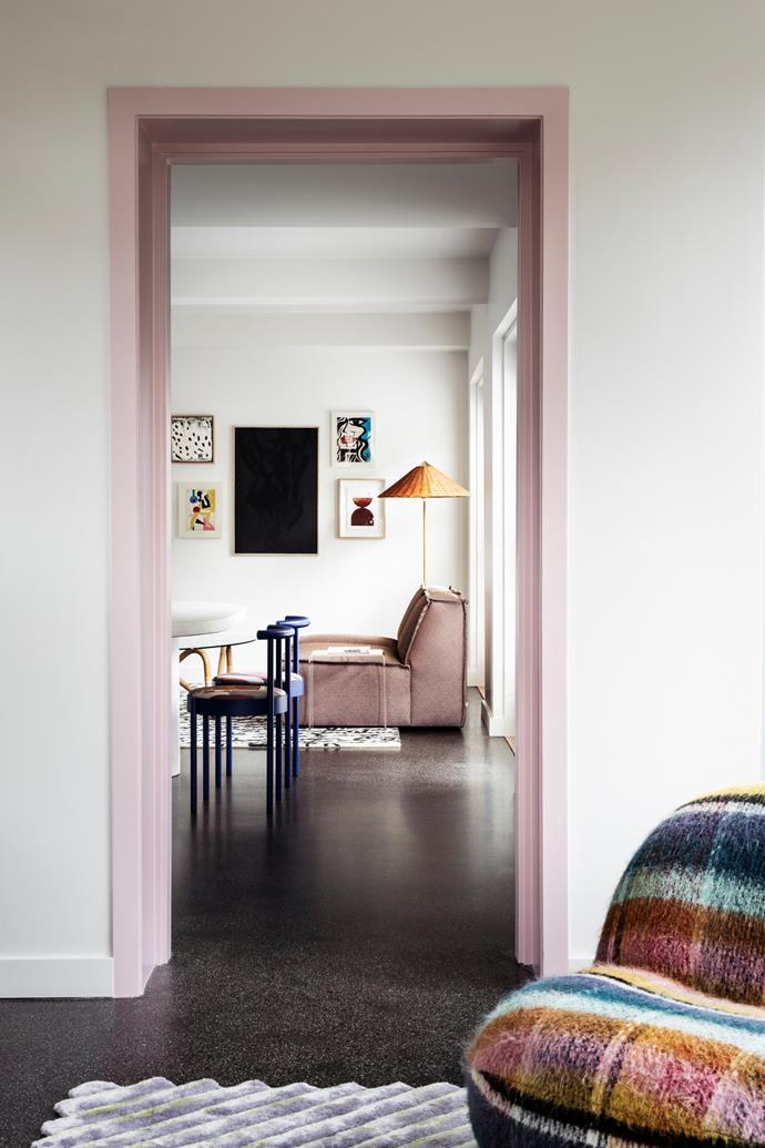 A doorway trimmed in Dulux Spice Girl leads to the library and study (opposite). A Rufus sofa from Harbro Furniture sits atop a Words rug from Nanimarquina, with a Gubi '9602' floor lamp from In Good Company behind. Artworks (clockwise from top left) are by Love Ludie, Anna Laurini, Jessalyn Brooks and Bobby Clark.
