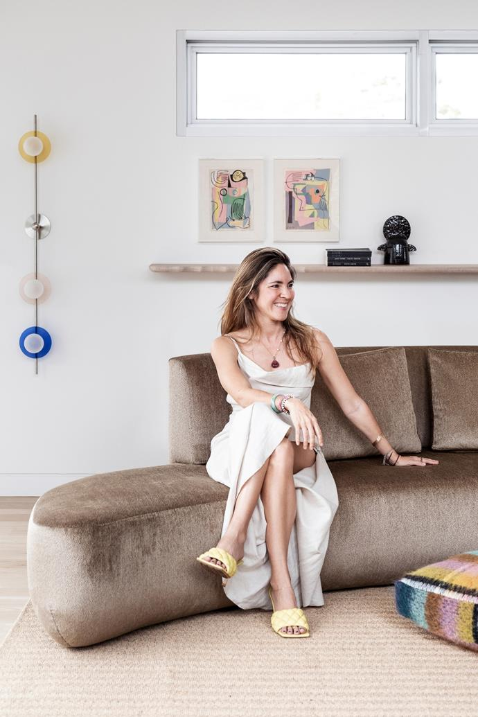"""""""This home is ideal for my family because there are multiple living spaces,"""" says Cheryl, pictured sitting on her custom sofa covered in Dedar velvet from South Pacific Fabrics. She wears a Jacquemus dress and Bottega Veneta shoes. Behind is a custom wall light by Giffin Design and figurative artworks by Jessalyn Brooks."""
