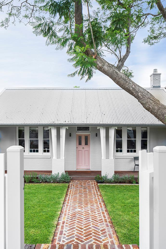 Homeowners Maddy and Sean chose a blush tone, Taubmans Pink Dust, for the front door of their sweet cottage in Sydney's inner-west. The exterior is painted Dulux Ghosting with DuluxSnowy Mountains on trims and picket fence. A concrete verandah has been replaced with decking in spotted gum. The path is paved in recycled bricks from Recycled Brick Centre, laid in a herringbone pattern.