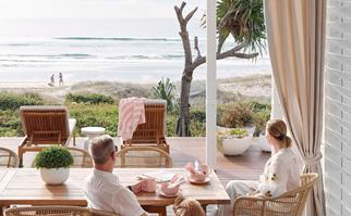 Couple sitting at dining table overlooking beach on the Gold Coast, QLD