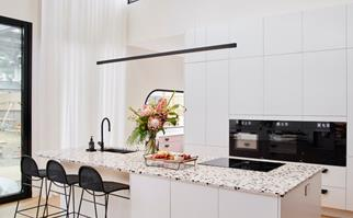 White kitchen with high ceilings and terrazzo island bench