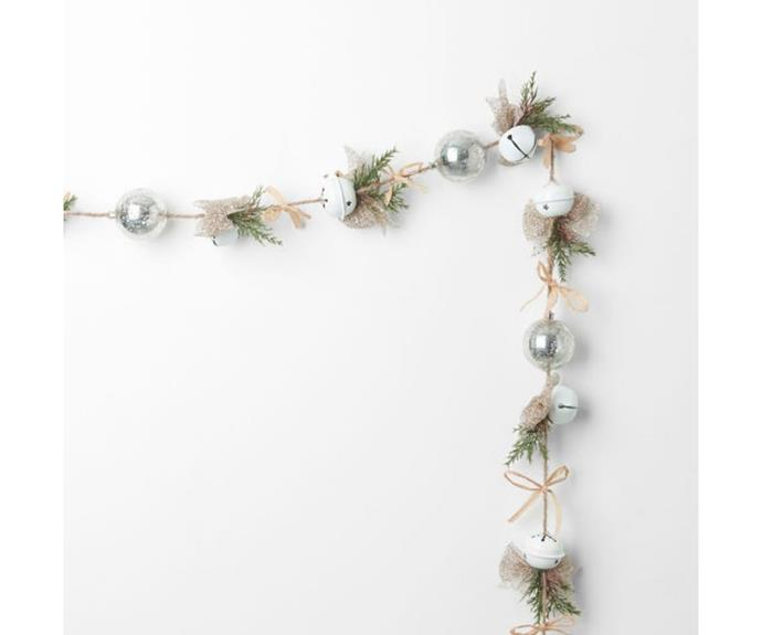"""**Bell Bow Jute String Garland, $29.99, [Bed Bath 'n Table]( target=""""_blank"""" rel=""""nofollow"""")**  This simple and elegant garland nails the Hamptons look in monochromatic magic. Sprigs of pine run along jute between cute little bows to add a touch of sparkle. White Christmas bells bring the jingle and beg to be hung on your front door or where they'll be nudged."""