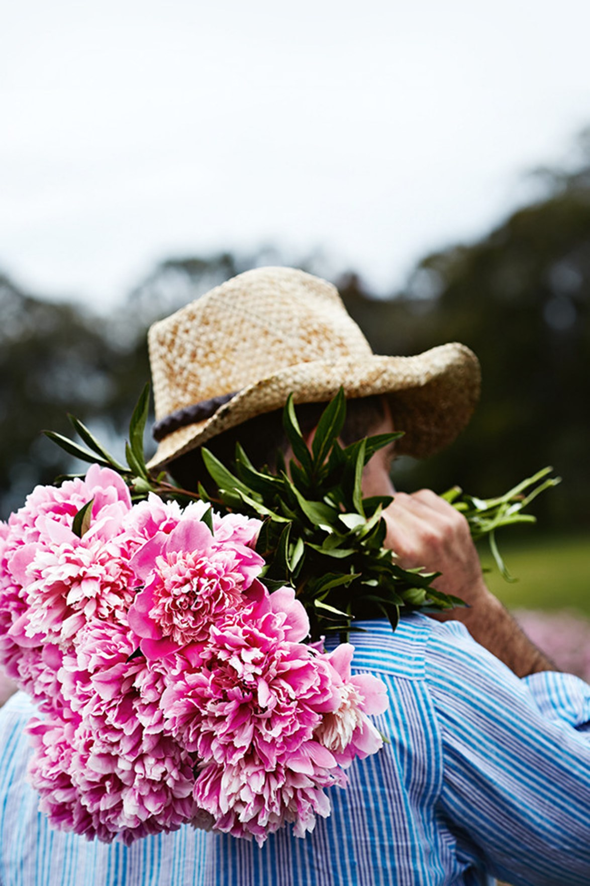 """A farmer with a bunch of peonies at [Spring Hill Peony Farm](https://www.homestolove.com.au/a-home-among-the-peonies-12183