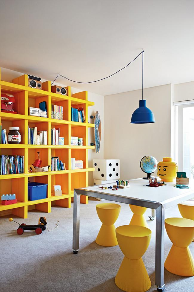 A floor to ceiling storage unit makes the most of this playroom, while the table features a central recess to store pencils and art supplies.