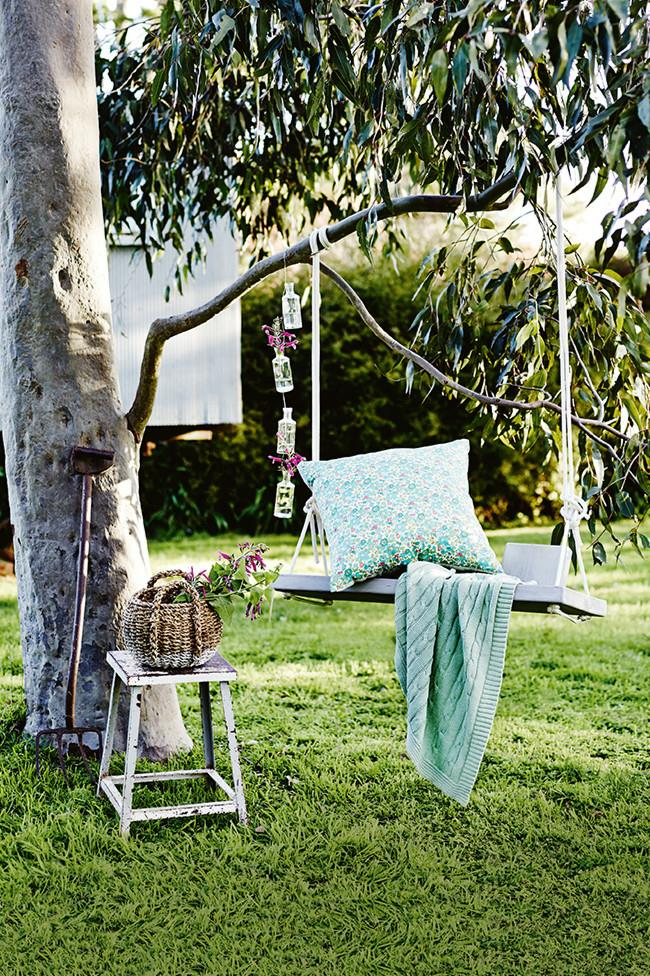 Hang a rustic swing from a tree branch and decorate with cushions, adding an elegant touch with some DIY hanging vases.