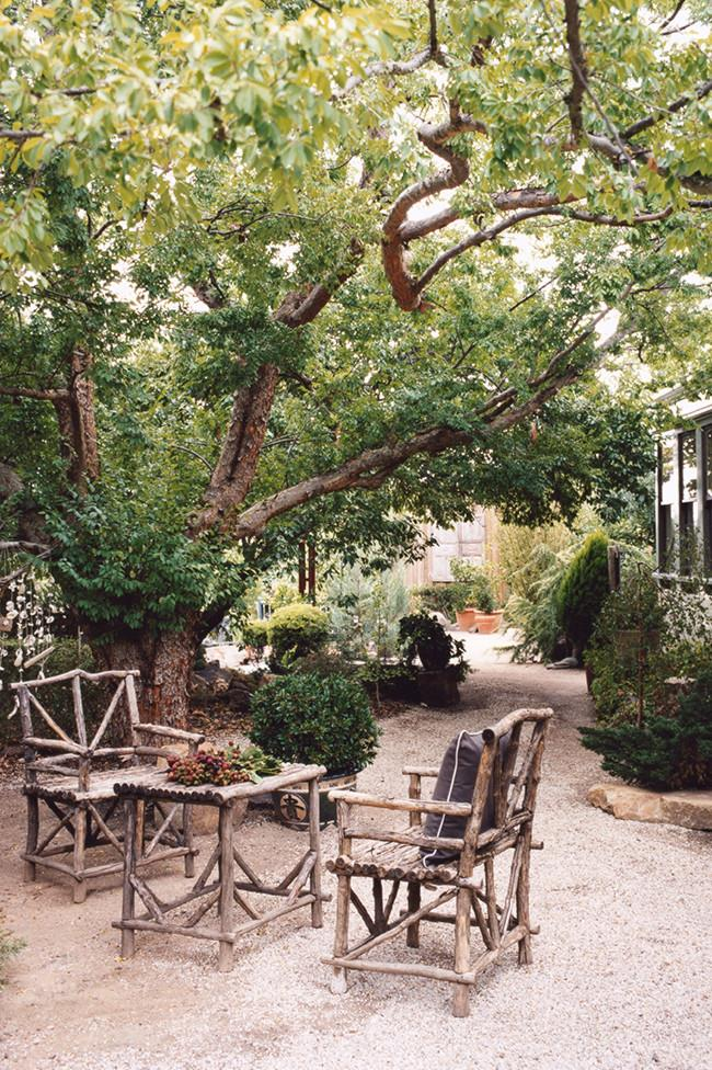 **16.** An old elm creates a shady spot for Indonesian stick furniture in this cottage garden. | Photo: Mark Roper