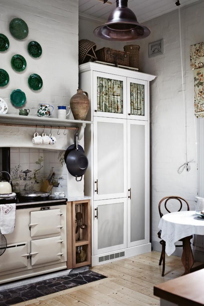At the heart of this home is a gas-fired Aga and handpainted tiles by Kathie Najar. Wedgwood 'Green Majolica' plates hang on the chimney breast. Try mixing crockery for an eclectic look. *Photo: Sharyn Cairns*