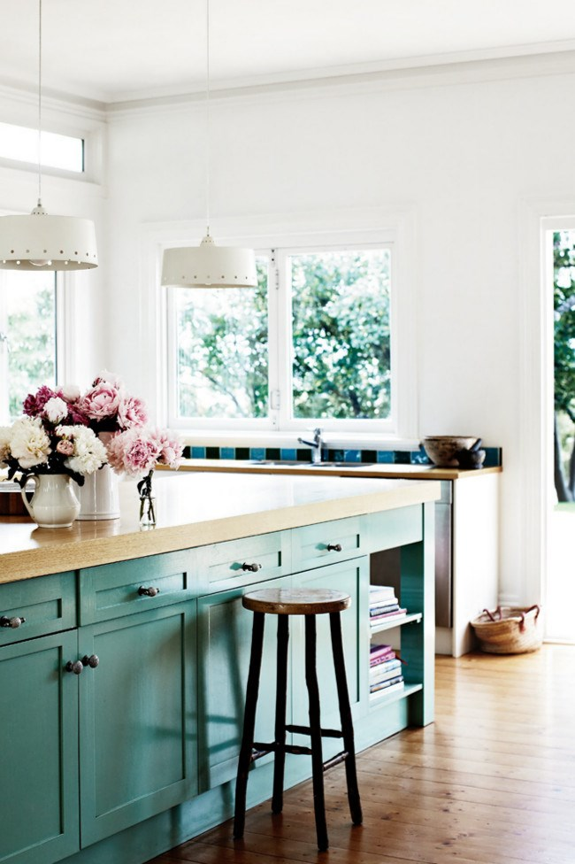 Clerestory windows flood light into the kitchen, where handpainted tiles from Aeria Country Floors in Sydney's Woollahra line the walls. The benchtop is made from Tasmanian oak and the cabinets are painted with old paint found in the shed. *Photo: Sharyn Cairns*