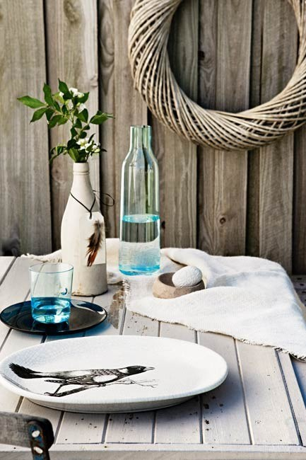 Combine driftwood, feathers, baskets and shades of blue and white. OB Collection 'Animal' platter, from [Orson & Blake](http://www.orsonandblake.com.au/). Holmegaard 'Minima' tumbler, from [Jarass](http://www.jarass.com.au/). Vintage beer bottle, from [Edit](http://www.edit-group.com.au/). Holmegaard 'Minima' decanter, from Jarass. Wreath, (large), from [Purdys Furniture](http://www.purdysfurniture.com.au/). | Photo: Sam McAdam-Cooper