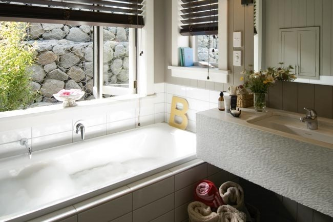 This small bathroom appears spacious through the clever use of horizontal lines and a high ceiling. A large mirror and vanity make this space-challenged room feel fit for a queen, while the use of natural materials such as stone and timber reflects the environment and brings the outdoors in.
