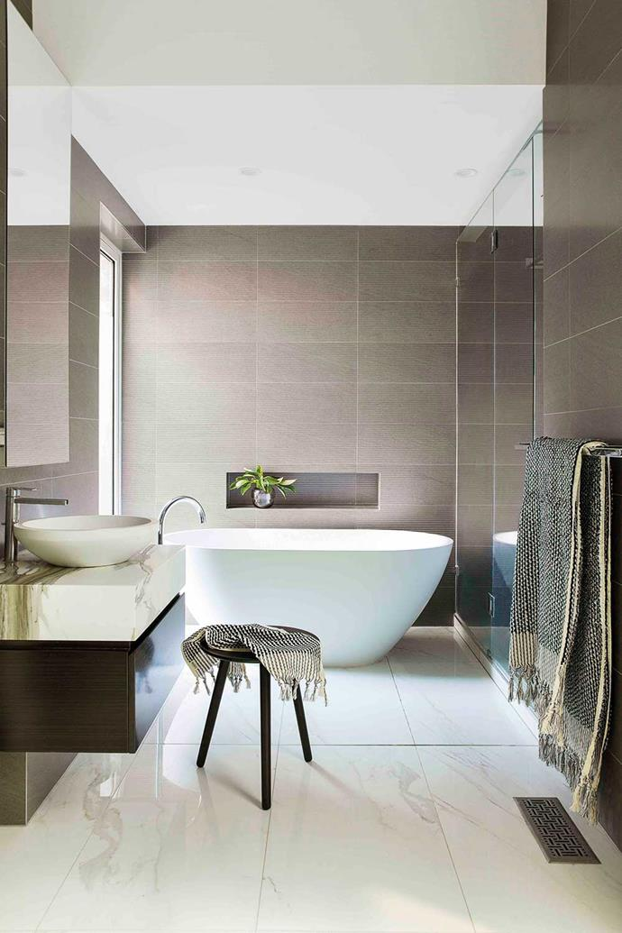 'Bologna' basin by Dado, with tapware by Gessi, a glossy floor in Calacatta marble and grey Basaltina Linea wall tiles