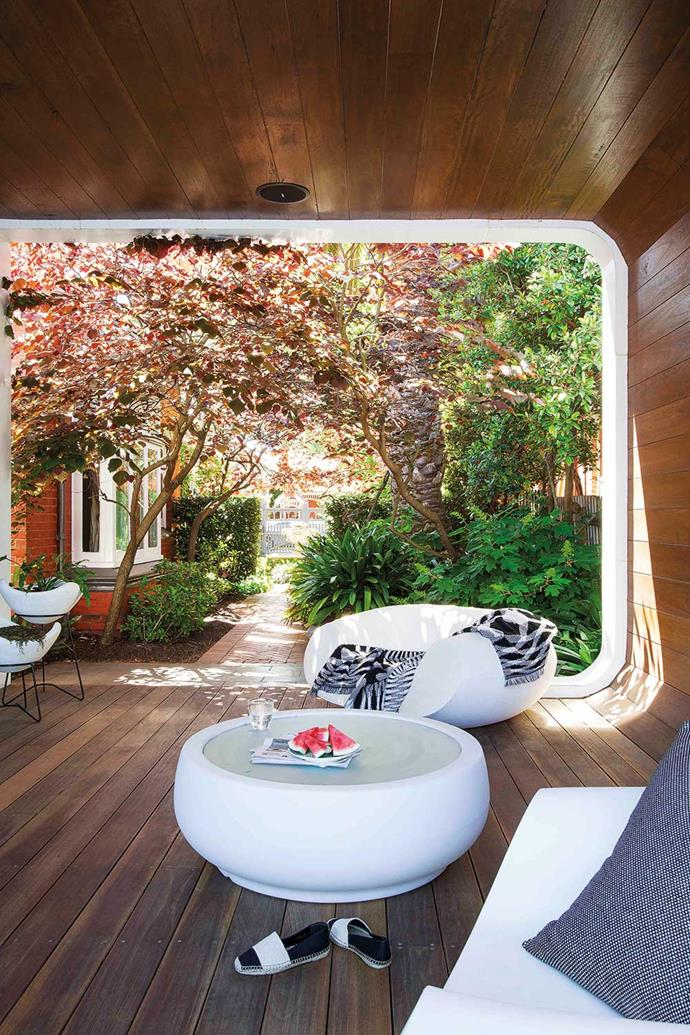 The oak lining of the curved outdoor cabana forms a seamless spot in summer