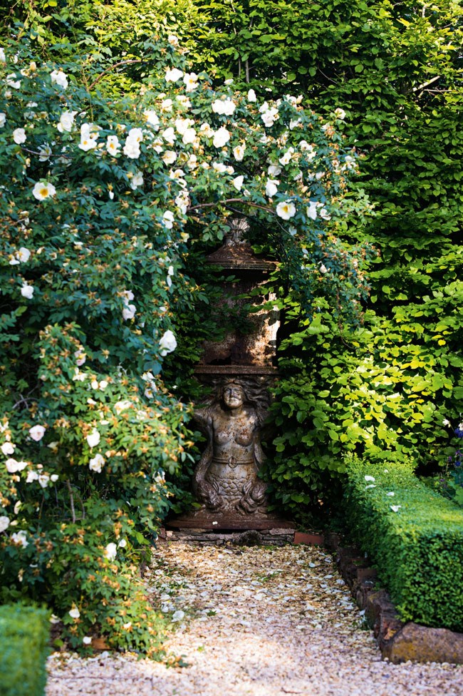 """A 'fruhlingsgold' rose sprawls over an antique statue at a manicured [country garden in Newlyn, Victoria](https://www.homestolove.com.au/a-flourishing-country-garden-in-newlyn-victoria-13541