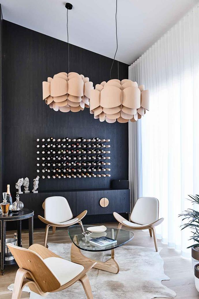 A wall of Evenex veneer in Black Caviar from Elton Group creates a chic backdrop for the striking custom-made oak dowel wine rack