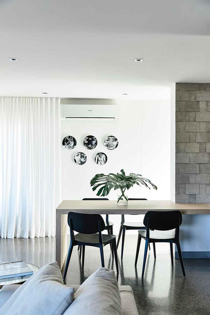 Connected to the island, a cantilevered table, surrounded by Billiani 'Doll' chairs, is ideal for casual meals