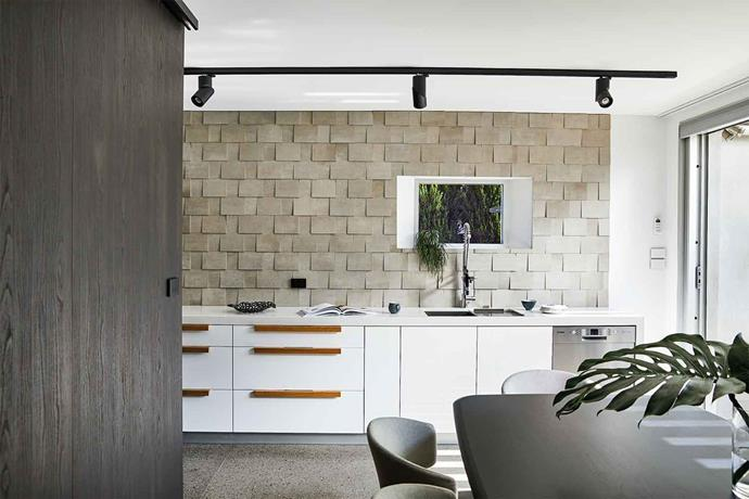 Lining the splashback of the kitchen, textured Prima Materia 'Cenere Mosaici' tiles from Disegno Casa contribute an organic feel