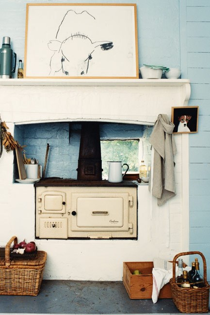 **Country kitchen** | A cow drawn by Jenny Bell rests atop the mantle over the country stove.