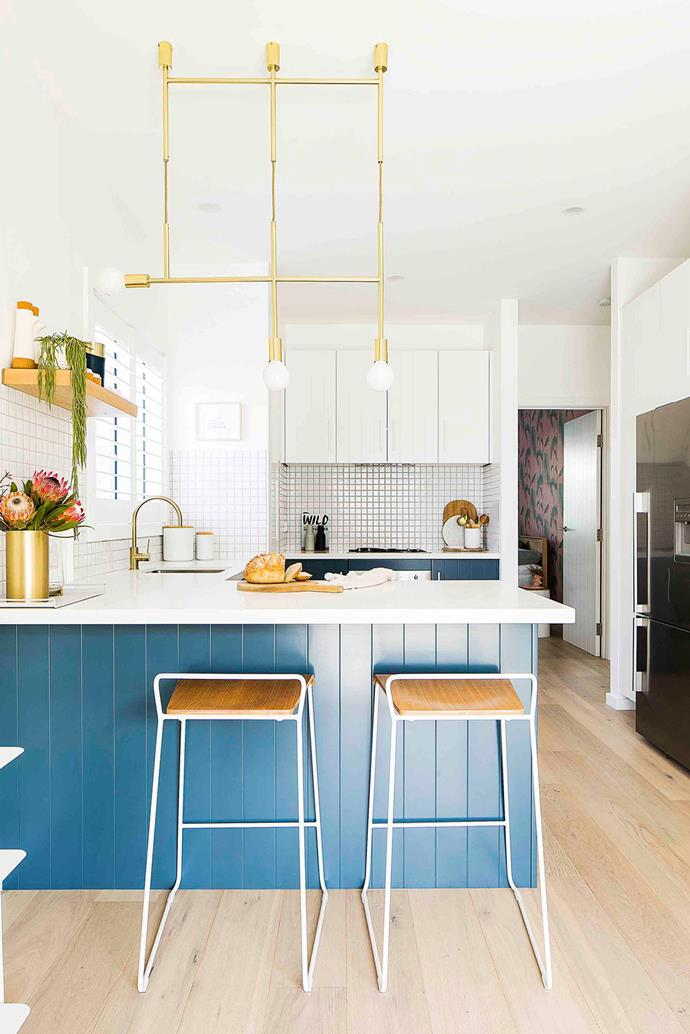 The kitchen, once clad in tired terracotta and monochrome, now pops thanks to cabinetry in deep blue Dulux Vipere, a 'Triple Kick' pendant light by Melbourne designer Volker Haug, Phoenix 'Lexi' tapware in brushed gold, and 'Transit' bar stools from Curious Grace.