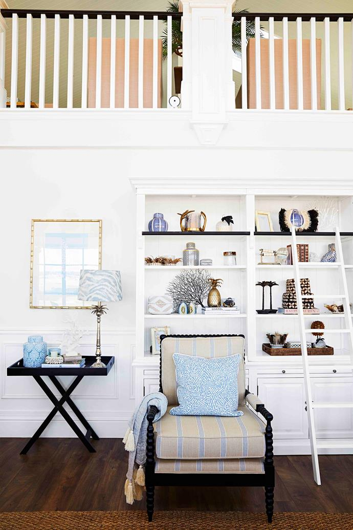 Library shelving, complete with a ladder, provides tiered surfaces to curate collections and create eclectic vignettes.
