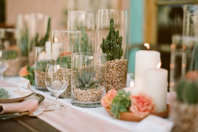 Filling vases of various heights with stones or beans will keep smaller plants in place. Add cacti and succulents in a range of shapes and display them alongside candles and fresh blooms for a memorable table setting.Image via [Green Wedding Shoes](http://greenweddingshoes.com/)