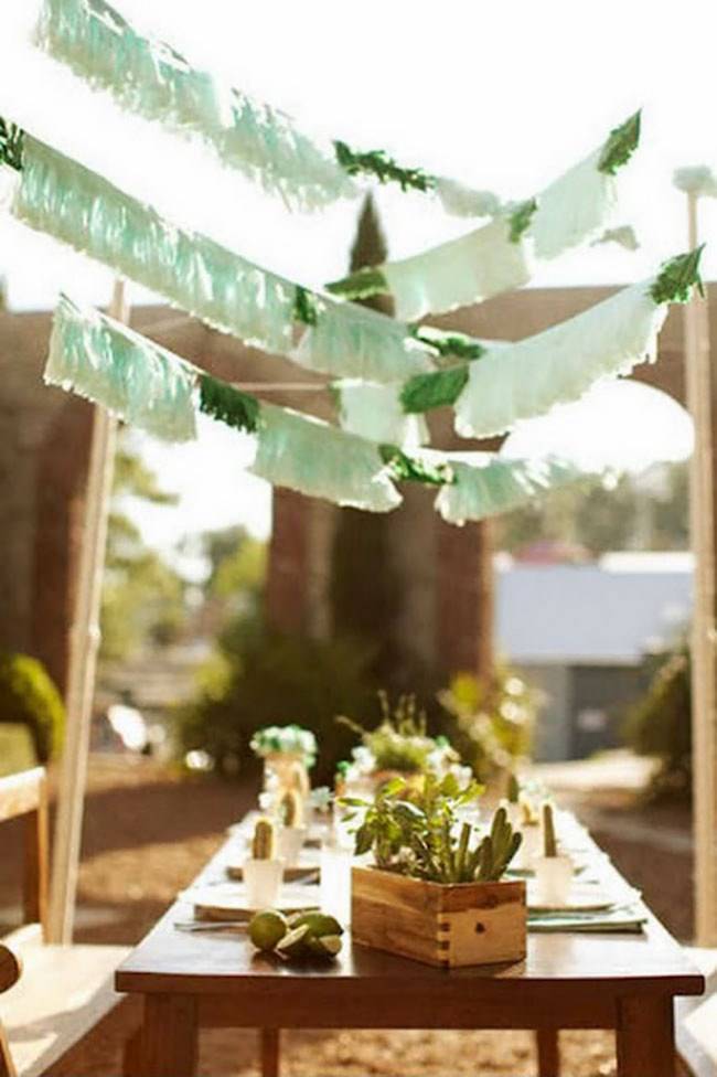 A predominantly green palette ties in the cacti with bunting hanging above, while natural wooden touches perfectly complement the earthy, calming colour scheme. Image via [Pinterest](https://au.pinterest.com/)