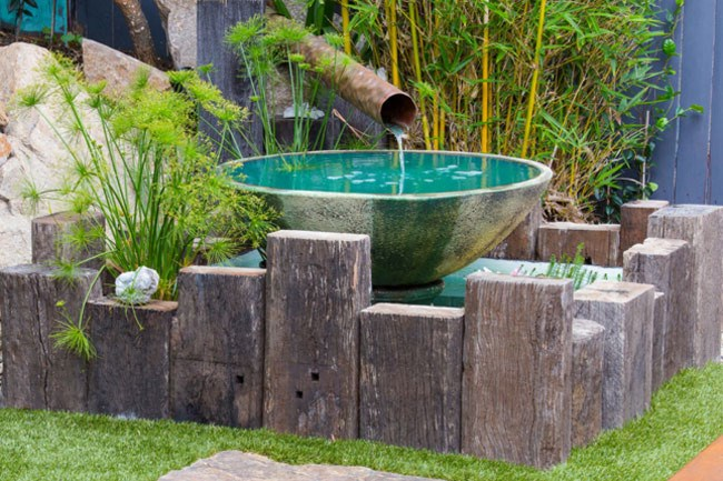 **3\. Water feature.** We designed and constructed a rustic timber edge border to add contrast to the smooth edges of the water bowl. The hammered copper pipe will patina over time. Aquatic plants and fish fill the pond.