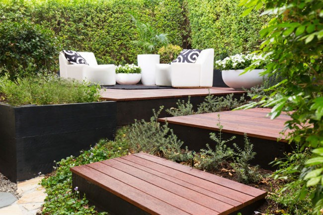 **9\. Modern entertaining deck.**Originally, this garden was an ususable steep slope. We built a flat timber entertaining area surrounded by planter boxes. Step platforms were used instead of a staircase - this creates space for low sprawling plants.