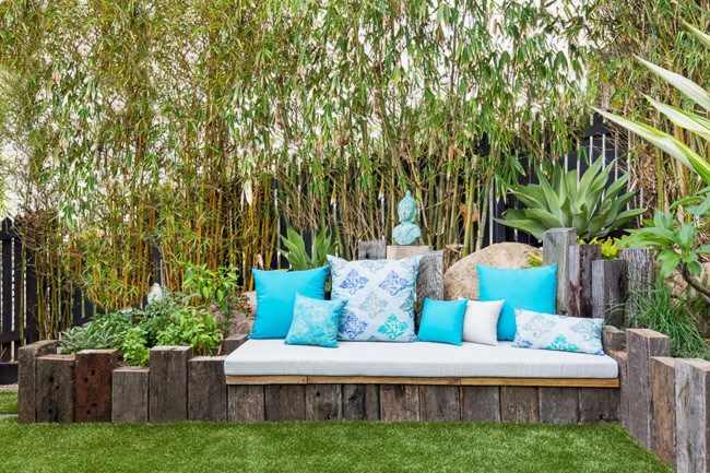 **6\. Outdoor seat.** The owner of this small garden wanted somewhere to relax in the sun. We made the seat from reclaimed ironbark railway sleepers. Cushions in aqua and gold add pops of colour and texture to the space. The sun lounger has aromatic herb gardens growing on either side of it.