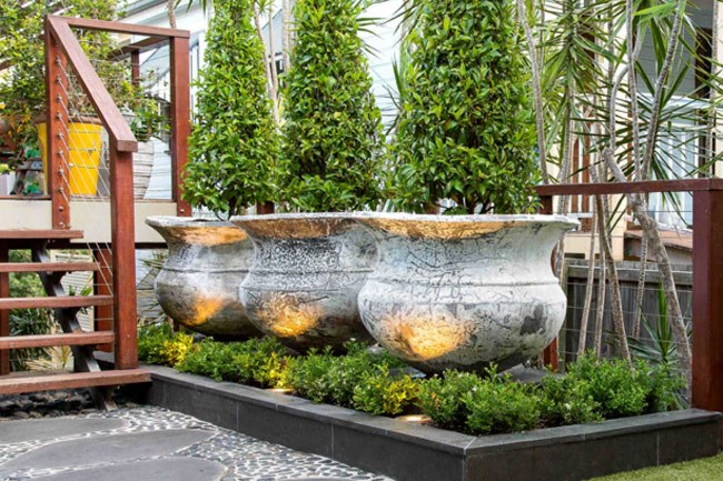 **7\. Entrance with wow factor.**Bluestone plinths were constructed to accommodate three large rustic pots with topiary port wine magnolias. The pot bases and plinths are softened by a small hedge of min min murraya.