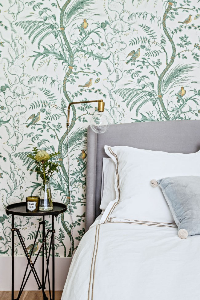 """<p class=""""p1"""">Subtle echoes can tie together disparate pieces. In this bedroom, golden notes in the wallpaper are matched by a light fitting, details on the white bed linen and a floral arrangement. </p>"""
