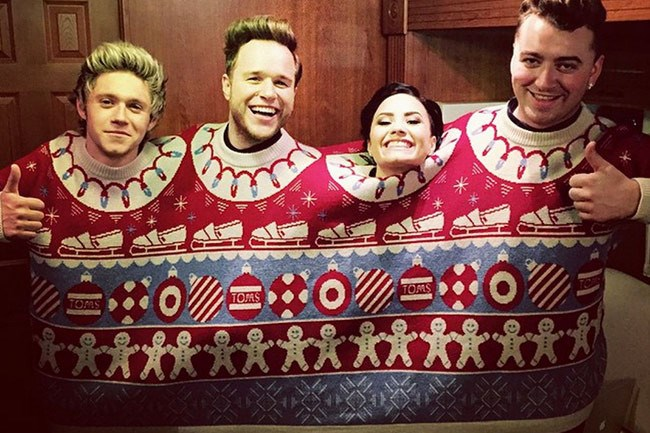 Singers Niall Horan, Olly Murs, Demi Lovato and Sam Smith get cosy in a festive jumper built for four. _Image from [Unreality TV](http://www.unrealitytv.co.uk/showbiz/one-directions-niall-horan-hooks-demi-lovato-olly-murs-sam-smith/)_
