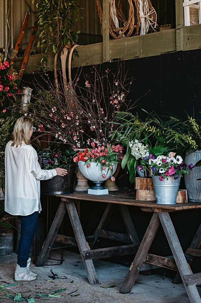 Freshly sourced flowers are stored and displayed in a variety of vessels on the farmhouse table in Aleksandra's shed in Dural.