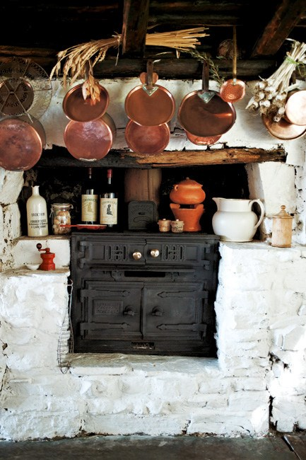 Copper pans hang above the wood stove. | Photo: Jared Fowler