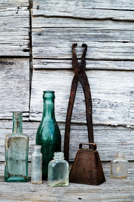 A collection of old bottles, a blacksmithing tool and a cow bell on the deck. | Photo: Jared Fowler