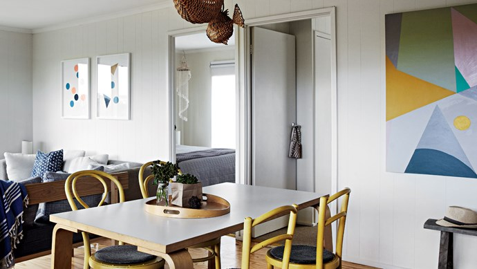 The kitchen table from IKEA is surrounded by second-hand chairs that Amber painted, including two bentwood chairs she saved from the tip. The cane fish suspended from the ceiling were found at Market Import in Melbourne. | Photo: Sharyn Cairns
