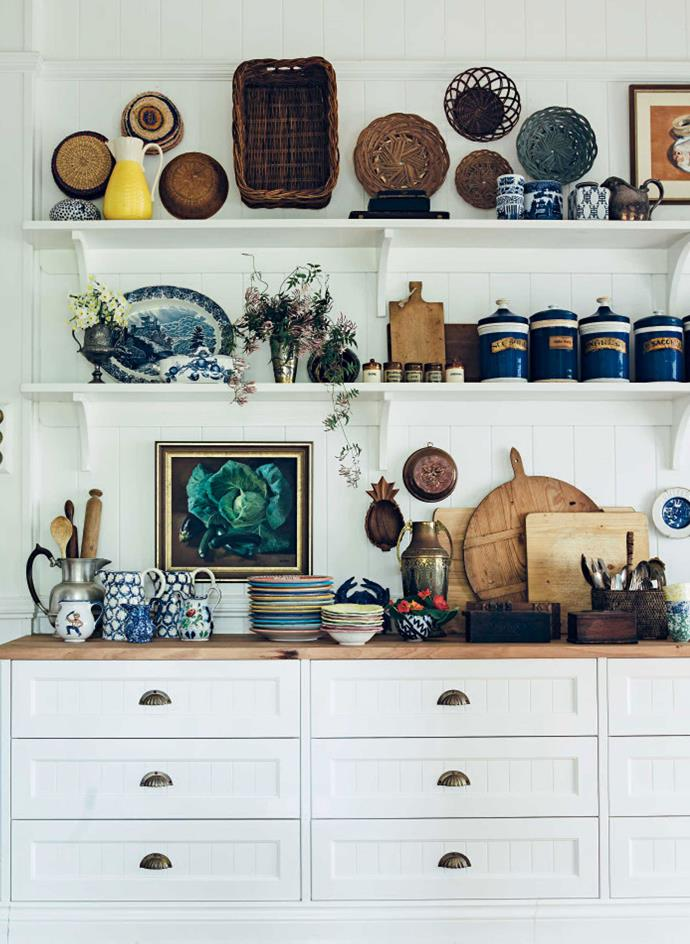 Kitchen shelves display woven baskets, apothecary jars, platters and jugs.