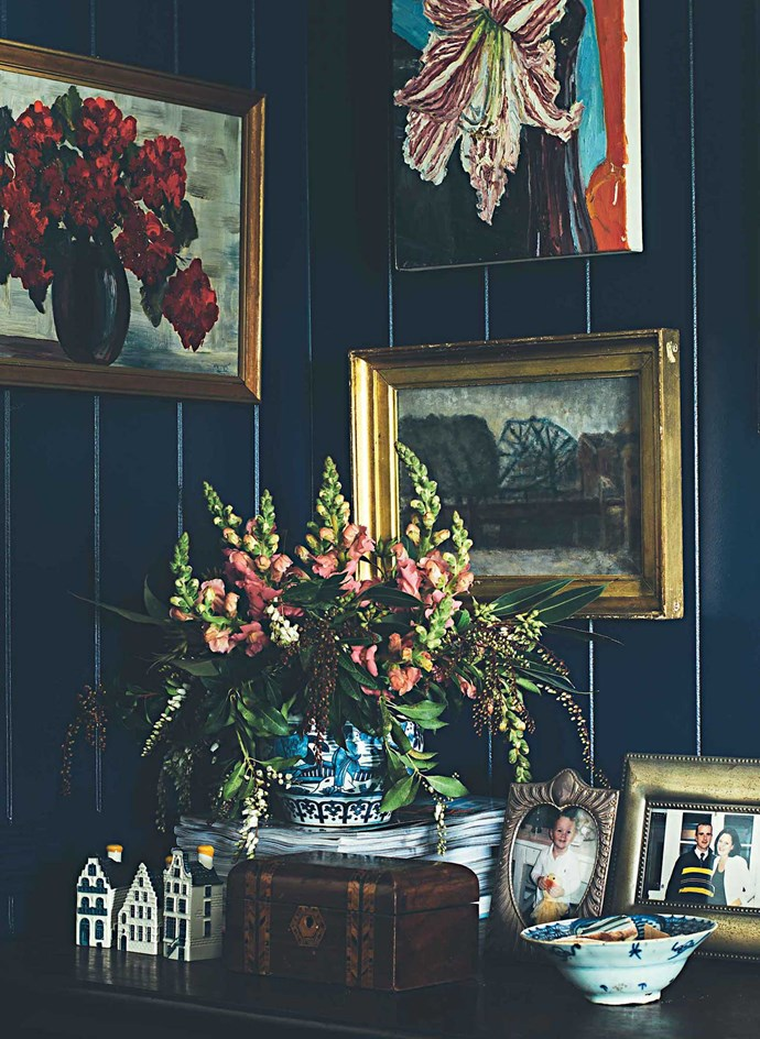 Two framed antique paintings in the navy blue bedroom. | Photo: Jared Fowler