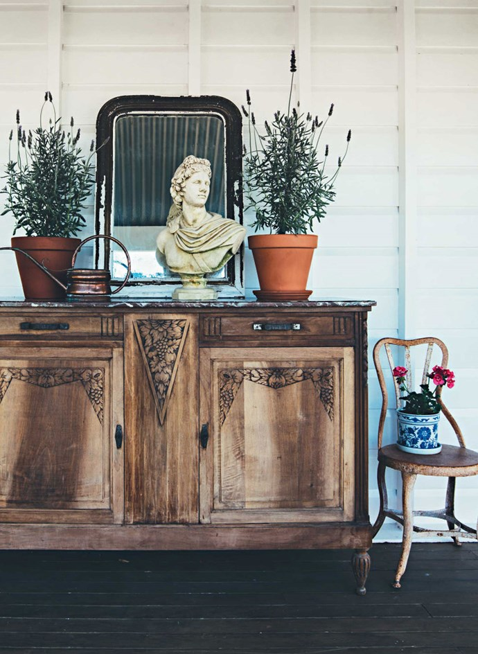 An old sideboard supports a French gilt mirror and a classical bust on the verandah. | Photo: Jared Fowler