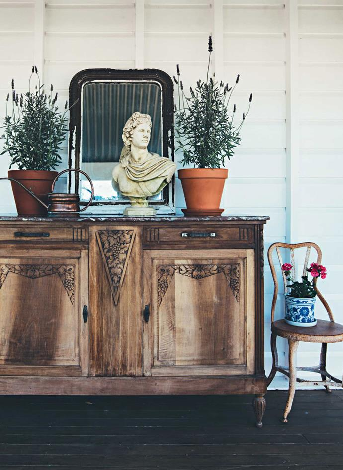 An old sideboard supports a French gilt mirror and a classical bust on the verandah.